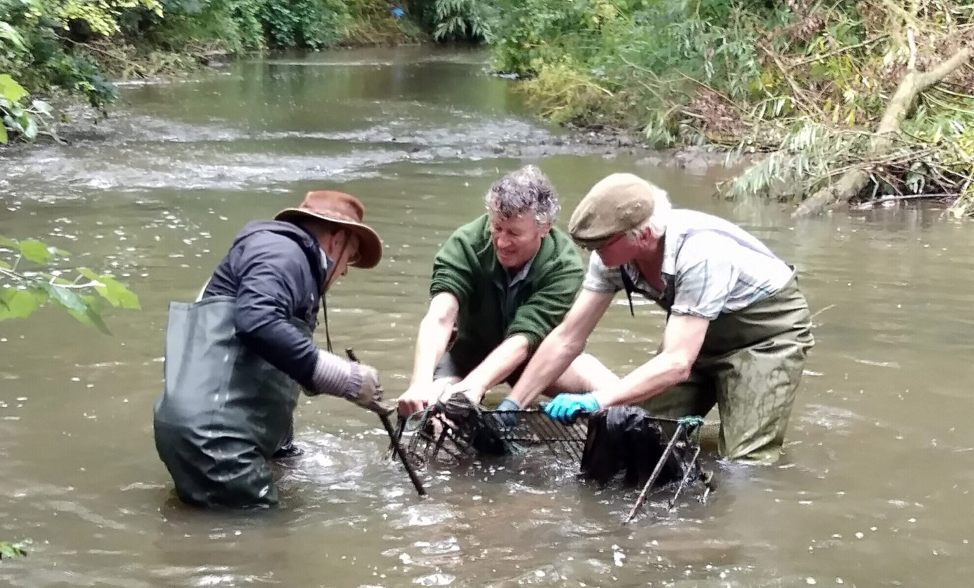 A photo of three men pulling debris from a river